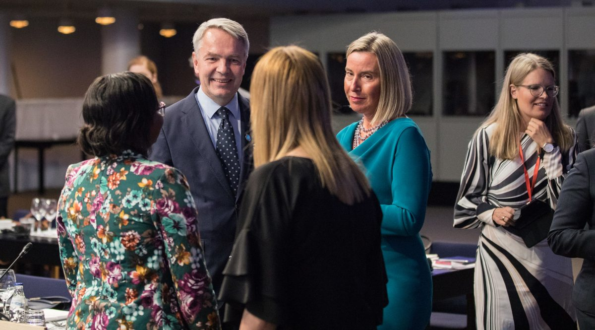 A man and three women standing and talking