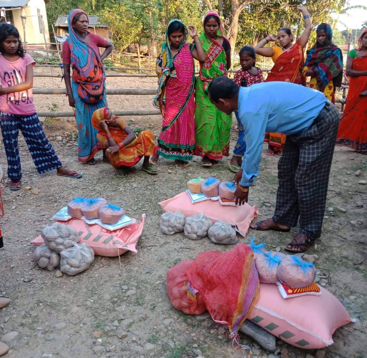 Man bending over relief supplies on the ground and women standing behind.
