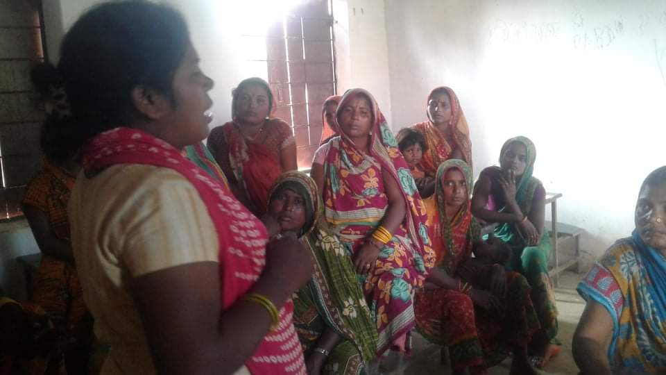 Woman talking to a group of women inside a house.