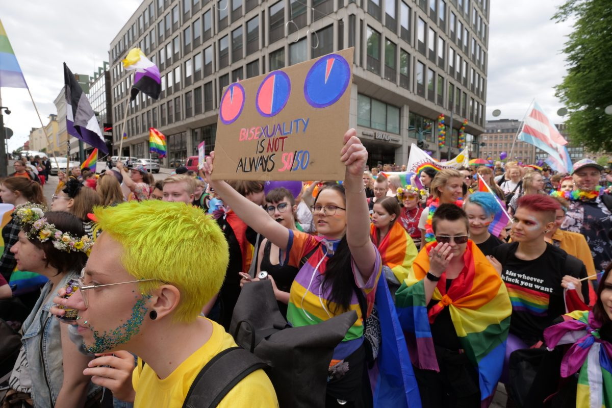 """Väkijoukko ja kyltti jossa lukee """"bisexuality is not always 50/50"""""""