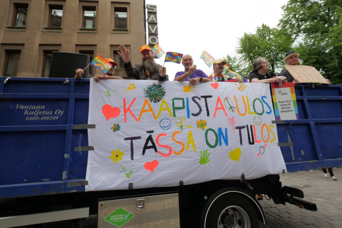 A truck with people in and a banner on the side