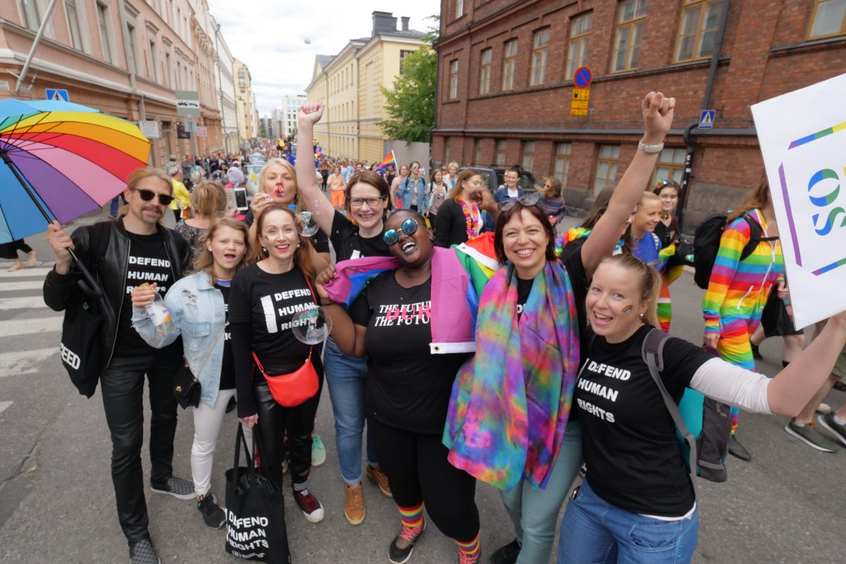 People smiling and holding rainbow flags and signs
